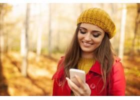 使用手机的微笑的妇女在公园在秋天期间_10672512