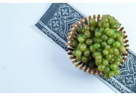 在篮子平的绿色葡萄在白色和厨房毛巾背景放
