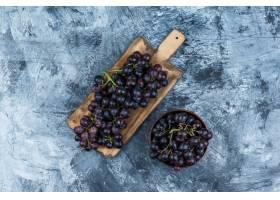 在黏土碗的黑葡萄在脏的膏药和切板背景平