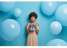 有卷发的懊恼黑皮肤妇女拿着蓝色高跟鞋鞋子