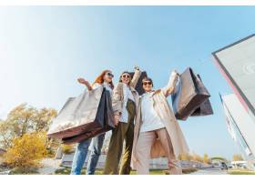 有购物袋的年轻愉快的妇女走在街道上的_10629151