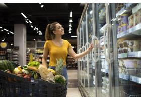 有购物车和用从冰箱的冰冻食物的女性人在杂