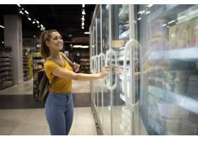 有购物车的女性人打开冰箱去食物在杂货店