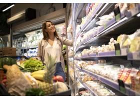 有购物车的妇女买的食物在超级市场