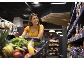 有购物车的妇女买的食物在超级市场_114505