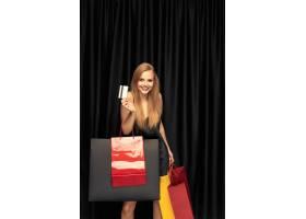 服装的年轻白肤金发的妇女在黑墙壁上购物