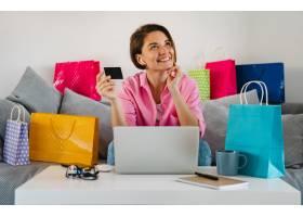 桃红色衬衣的愉快的微笑的妇女在家在家中的_14452622
