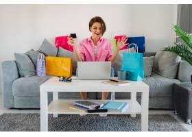 桃红色衬衣的愉快的微笑的妇女在家在家中的_14452634